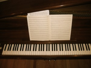 piano keyboard with sheets of music